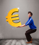 Good-looking boy holding a big 3d gold euro sign Stock Image