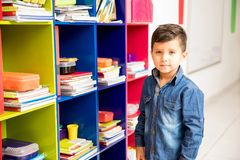 Good looking boy ready for school. Portrait of a handsome Hispanic preschool boy grabbing some of his books for class Royalty Free Stock Photo