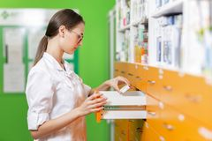 A good looking brown-haired girl with glasses,dressed in a medical overall,stands by a locker and looks for something. stock photography