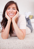 Good looking brunette female posing while lying Royalty Free Stock Images