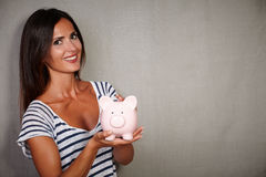 Good-looking brunette lady holding a moneybox Stock Photo