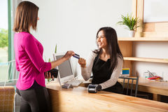 Good looking brunette paying with credit card Stock Photography