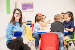 Kindergarten teacher ready for class. Good looking brunette teaching kindergarten to a group of students and looking happy stock image