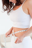 Good looking brunette woman measuring her belly Stock Images