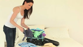 Good looking brunette woman packing up her suitcase Stock Images