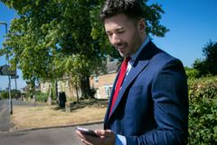 Handsome young excutive, business man, in blue suit looks at his mobile phone, device stock photography