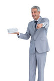 Good looking businessman offering gift and pointing at camera Royalty Free Stock Photo