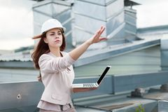 Good Looking Businesswoman In Beige Suit, Brown Trousers And Helmet Sit On The Roof And Hold Laptop Stock Image