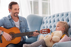 Good looking caring father singing for his daughter. Pleasurable entertainment. Good looking delighted caring father holding a guitar and playing a song while Stock Image