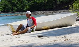 Good looking castaway man sitting in the beach by a wrecked boat waiting for help with ocean and jungle in the background. Sea and sand in Costa Rica, lost in stock image