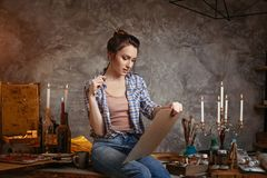 Good-looking cheerful professional young female artist working on new creative project, drawing, feeling inspired. Creative concept. Drawing supplies, oil Royalty Free Stock Images