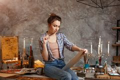 Good-looking cheerful professional young female artist working on new creative project, drawing, feeling inspired. Creative concept. Drawing supplies, oil Royalty Free Stock Photos