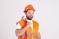 Good Looking Construction Worker with Bricklayer Hammer. Handsome Construction Worker in Safety Helmet and Orange Reflex Jerkin is Holding a Hammer Isolated on Royalty Free Stock Photo