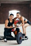 Good looking couple with bottles of water and phones looking at the camera. During workout royalty free stock photography