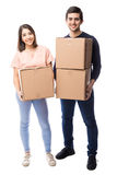 Good looking couple carrying some boxes. Full length view of a young couple carrying some boxes and moving in together royalty free stock photography