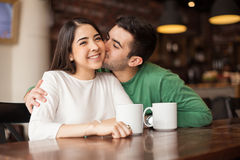 Good looking couple in a coffee shop. Young men kissing her girlfriend in the cheek while having some coffee together in a cafe Stock Photography