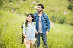 Hispanic couple trekking. Good looking couple enjoying the afternoon trekking together at the mountain Stock Photos