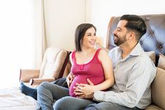 Smiling Pregnant Couple Looking At Each Other stock photography