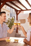 Good looking couple raising their glasses together. Good looking young couple raising their glasses in a cheers while they are sitting at a table with bowls of royalty free stock photos