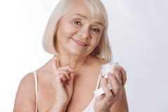 Good looking delighted woman applying cream on her neck Stock Images