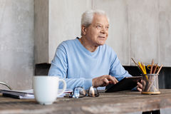 Good looking elderly man enjoying a productive morning. Exciting start. Senior savvy energetic gentleman using his tablet for reading some news while sitting at Royalty Free Stock Images