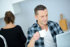 Good-looking enterpreneur working on laptop while having coffee and breakfast. Man Stock Photography
