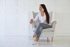 Good looking female in casual outfit speaking on smartphone sitt Stock Images