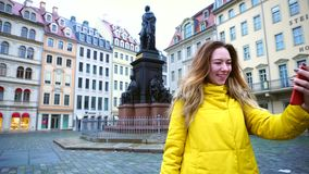 Good-looking female chatters in videocall over phone and shows surroundings of European old city Dresden on winter day. Portrait of pleasing Young woman who stock video