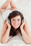 Good looking female with headphones lying Stock Image