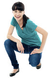 Good looking female model in squatting posture Stock Images