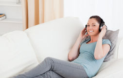 Good looking female using headphones while lying Stock Image