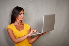 Good-looking female using laptop while standing Royalty Free Stock Photo