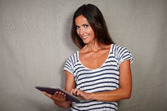 Good-looking female using tablet while standing Royalty Free Stock Photo