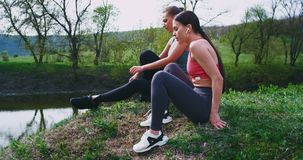 Good looking and with fit bodies two ladies enjoying the time together in amazing nature place after a hard workout
