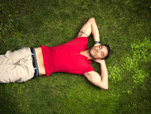 Good looking, fit male model relaxing lying on the grass Royalty Free Stock Photo