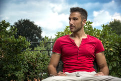 Good looking, fit male model sitting on bench Royalty Free Stock Photos