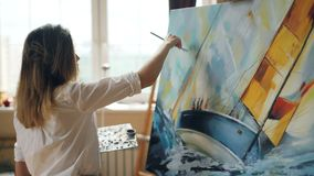 Good-looking girl artist is busy painting seascape on canvas using color palette, brush and canvas on easel working in. Nice studio. Talented people and stock footage