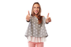 Good-looking girl giving acceptance with thumbs up hand gesture. Mid shot of good-looking girl who is giving two thumbs up while standing over white background Stock Photo