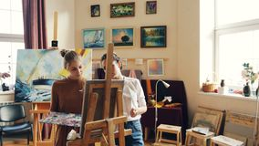 Good-looking girl is learning to paint having class with experienced female teacher skillful painter, people are working stock video footage