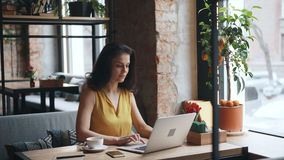 Good-looking girl working with laptop computer in cafe typing looking at screen. Good-looking girl student is working with laptop computer in cafe typing looking stock footage