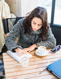Good looking girl writing something on a notebook with a cup of cappuccino Stock Photography