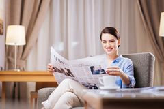 Good looking gorgeous woman evaluating news. Breaking news. Glad brunette jolly woman sitting at the armchair while looking at the newspaper and holding it royalty free stock photos