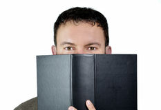 Good looking guy behind book. Handsome young man behind a big book, isolated on white Stock Photos