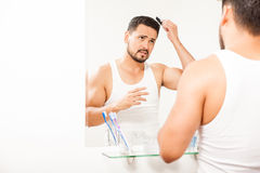 Good looking guy combing his hair. Young man with a beard combing and styling his hair in front of a mirror in a bathroom Stock Photos