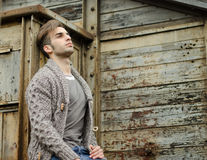 Attractive young man against rusty metal and wooden walls Stock Photos