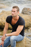 Good looking guy sitting on rock by the sea Stock Photos