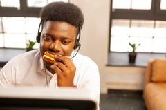 Good looking handsome man having a tasty snack. Tasty sandwich. Good looking handsome man having a tasty snack while being at work royalty free stock photo