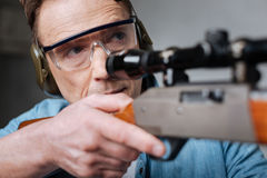 Good looking handsome man wearing safety glasses. Protective equipment. Good looking handsome pleasant ma wearing safety glasses and aiming with his gun while Royalty Free Stock Photography