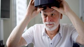 Good-looking handsome senior man in white takes off VR 360 glasses at home. Active elderly people