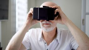 Good-looking handsome senior man in white using VR 360 glasses at home. Active modern elderly people. Concept. Seeing something unusual and exciting, learning stock video